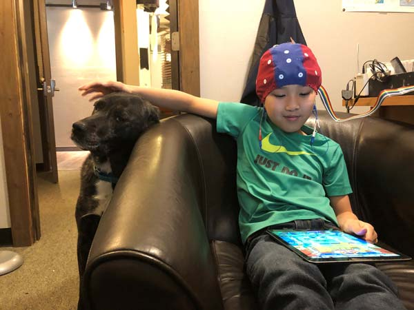 Preteen boy with dog on the couch