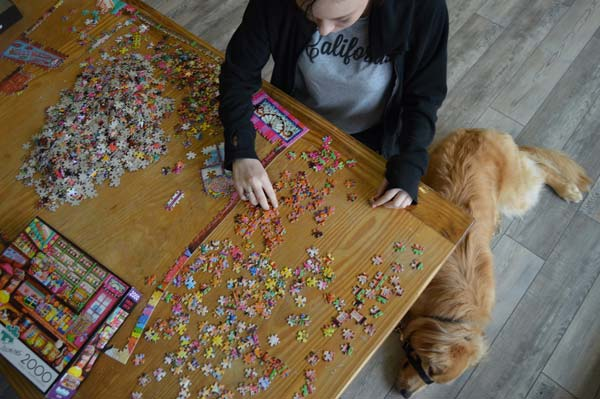 Teen girl putting a puzzle together while dog rests