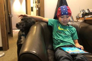 Preteen boy undergoing neurofeedback with his canine